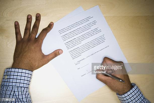 High angle view of a mid adult man's hand writing on paper