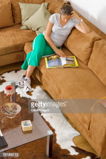 High angle view of a mid adult woman sitting on a couch and reading a book : Foto de stock