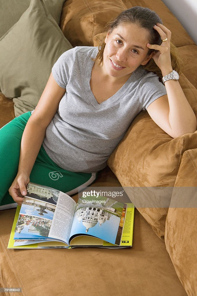 High angle view of a mid adult woman sitting on a couch and smiling : Stock Photo