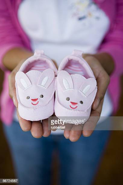 High angle view of a person holding baby shoes