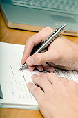 High angle view of a person's hand filling up a form with a pen
