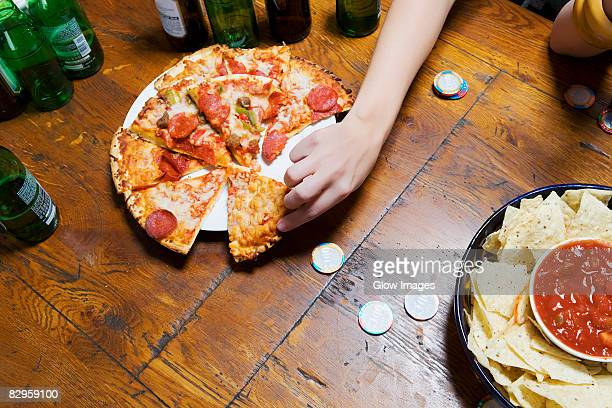 High angle view of a person's hand picking up a pizza slice