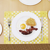 high angle view of a plate of fried eggs with hash browns and bacon
