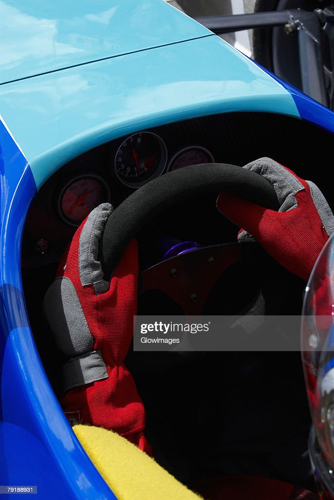 High angle view of a racecar driver's hands holding steering wheel of a racecar : Foto de stock