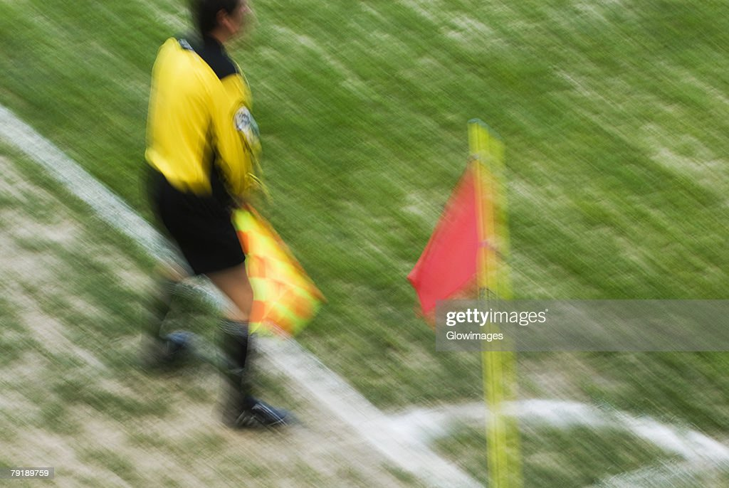 High angle view of a referee standing and holding a flag : Foto de stock
