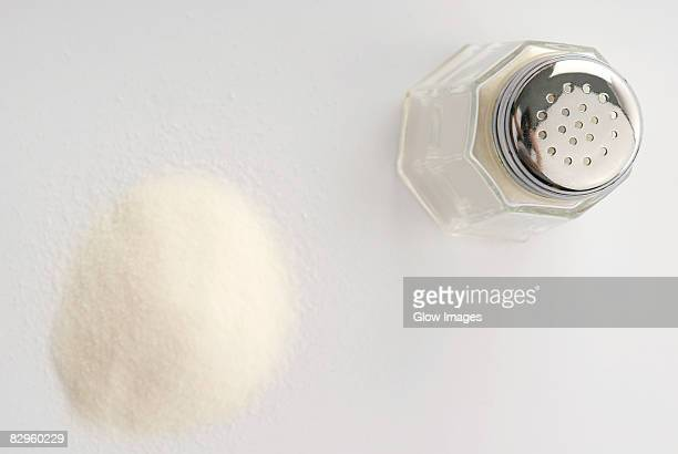 High angle view of a salt shaker with a heap of salt