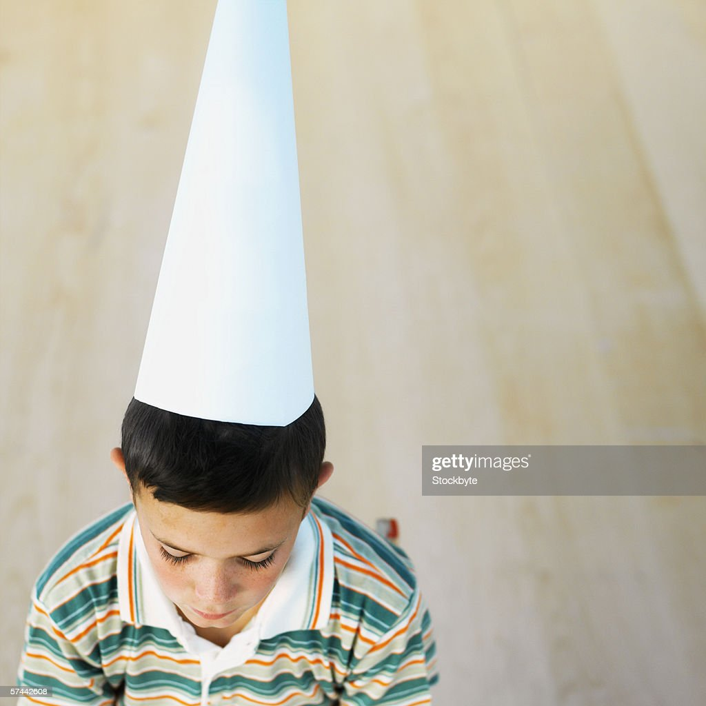 High angle view of a schoolboy (8-9) wearing a dunce cap