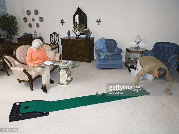 High angle view of a senior man playing golf in the living room