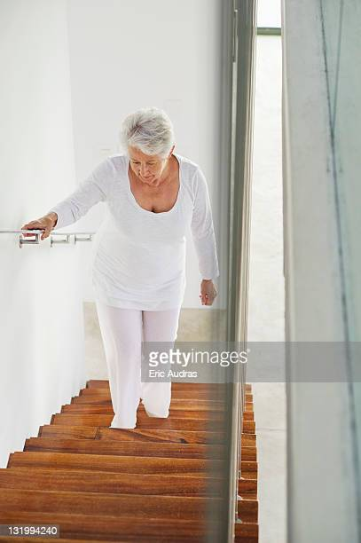 High angle view of a senior woman moving up staircases