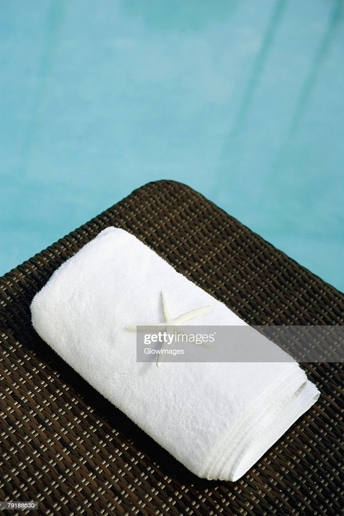 High angle view of a starfish with a towel on a lounge chair at the poolside : Foto de stock