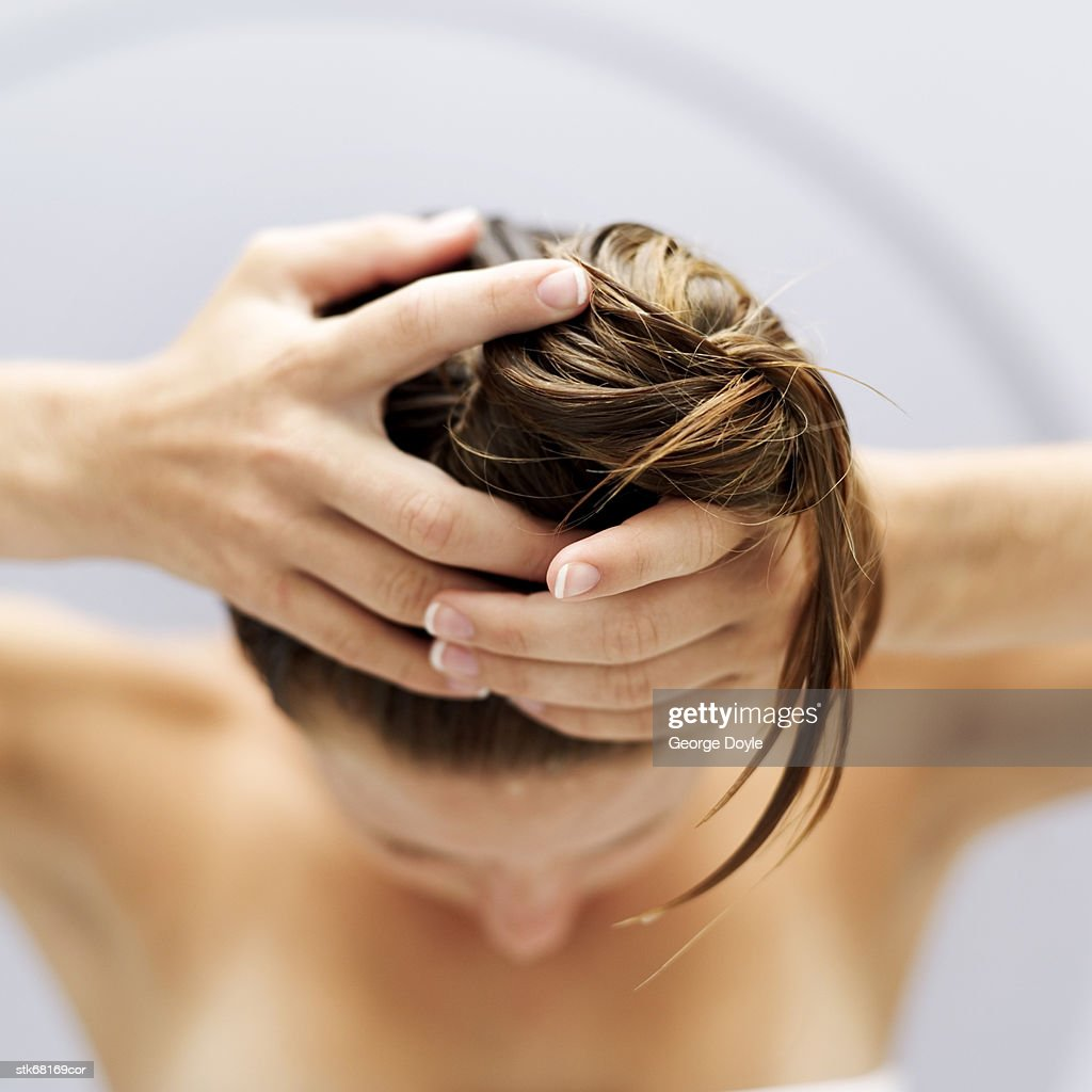 high angle view of a woman piling her hair up into a bun : Stock Photo