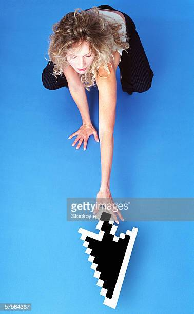 high angle view of a woman reaching out for the computer cursor on the floor
