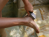 High angle view of a woman scrubbing sole of her foot