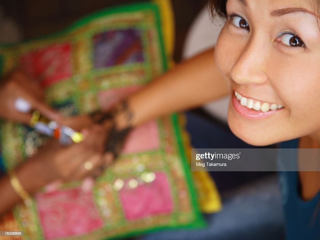 High angle view of a woman's hand applying henna tattoo on a mid adult woman's hand : Stock Photo