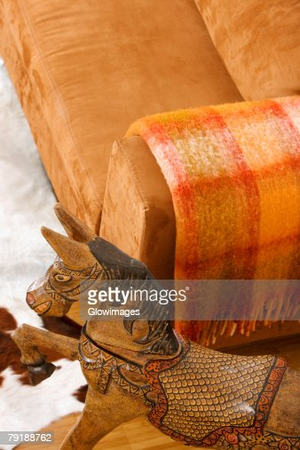 High angle view of a wooden horse near a couch : Stock Photo