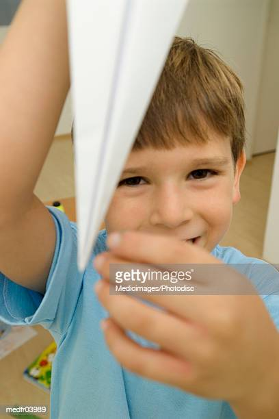 High angle view of a young boy holding up a paper plane