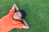 High angle view of a young boy lying on a lawn