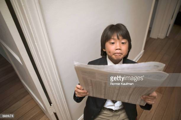 High angle view of a young boy reading the newspaper