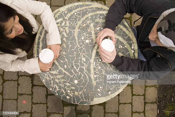 High angle view of a young couple holding cups of cappuccino