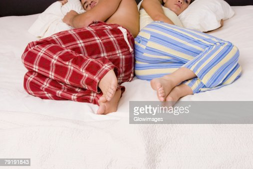 High angle view of a young couple lying back to back on the bed : Foto de stock