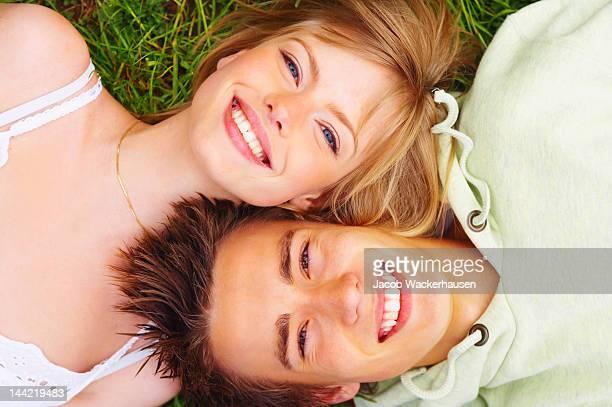 Vue grand angle d'un jeune couple allongé sur l'herbe