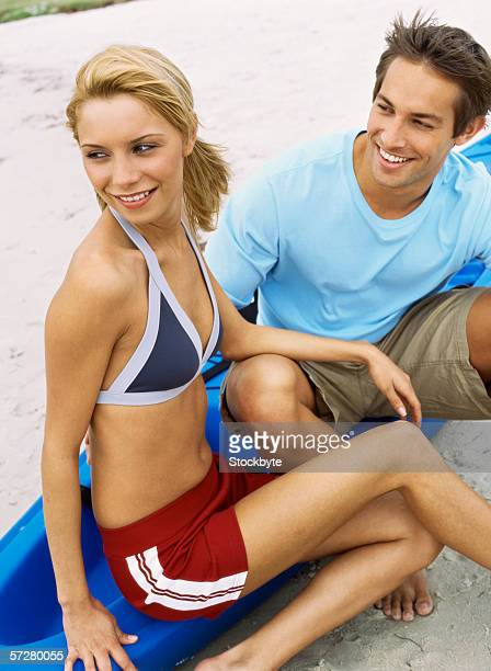 High angle view of a young couple on the beach, sitting on a canoe