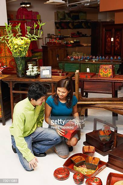 High angle view of a young man and a young couple choosing merchandise in a store