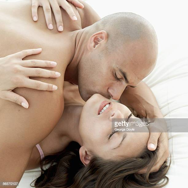 high angle view of a young man kissing a young woman's neck
