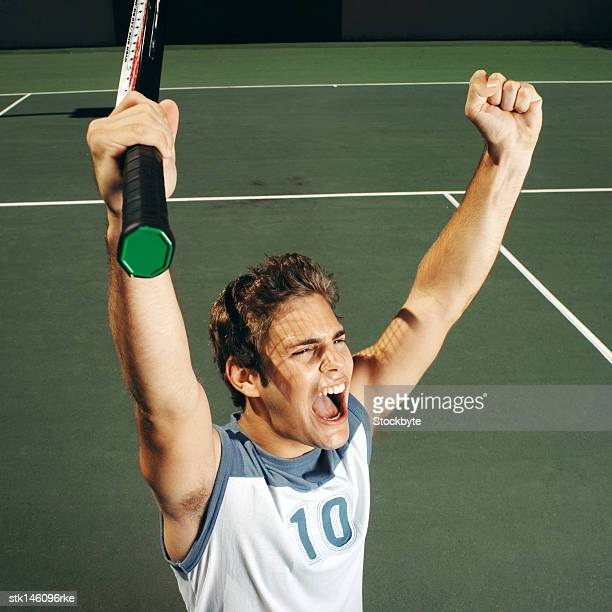 high angle view of a young man raising his arms during a game of tennis