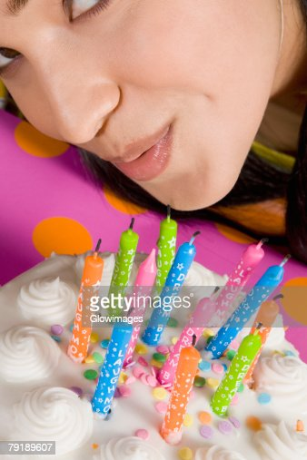 High angle view of a young woman blowing candles on a birthday cake : Foto de stock