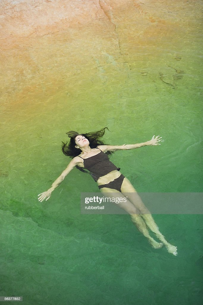 High angle view of a young woman floating on the water : Stock Photo