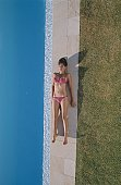High angle view of a young woman lying beside a swimming pool