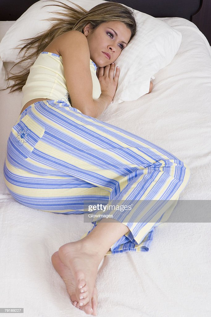 High angle view of a young woman lying on the bed : Stock Photo