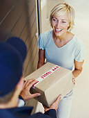 high angle view of a young woman receiving a package from a delivery man