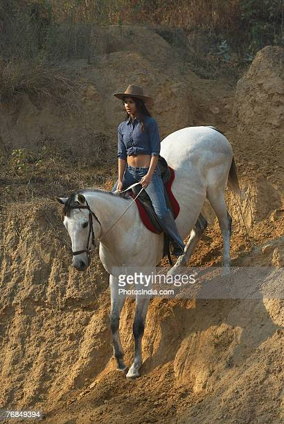 High angle view of a young woman riding a horse