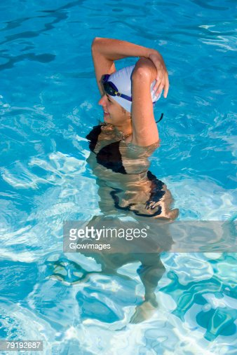 High angle view of a young woman standing in a swimming pool and smiling