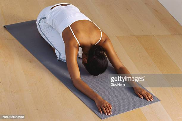 High angle view of a young woman stretching on a floor mat