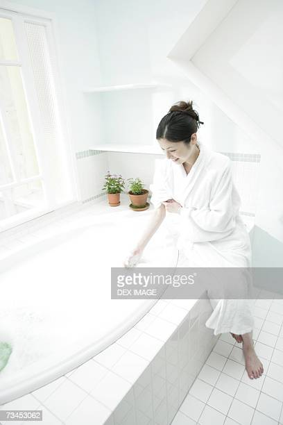 High angle view of a young woman waving her hand in a bubble bath