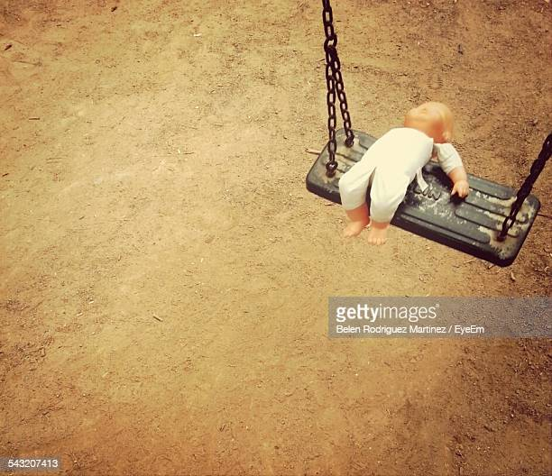 High Angle View Of Abandoned Doll On Swing
