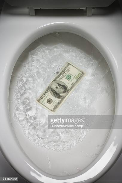 High angle view of an American dollar note floating in the toilet bowl