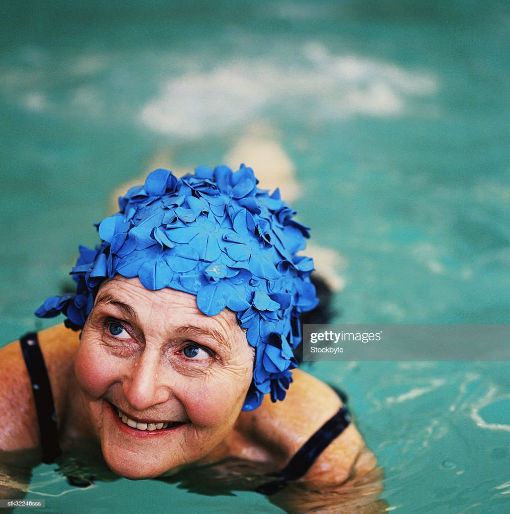 high angle view of an elderly woman in the swimming pool; smiling : Stock Photo