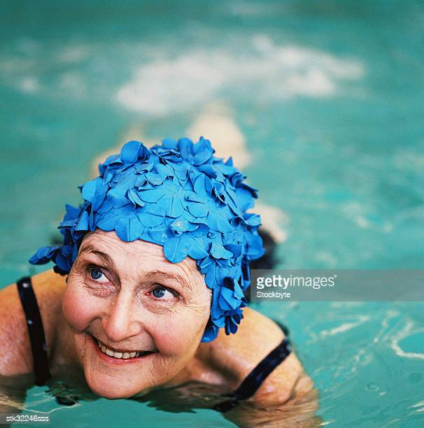 high angle view of an elderly woman in the swimming pool; smiling