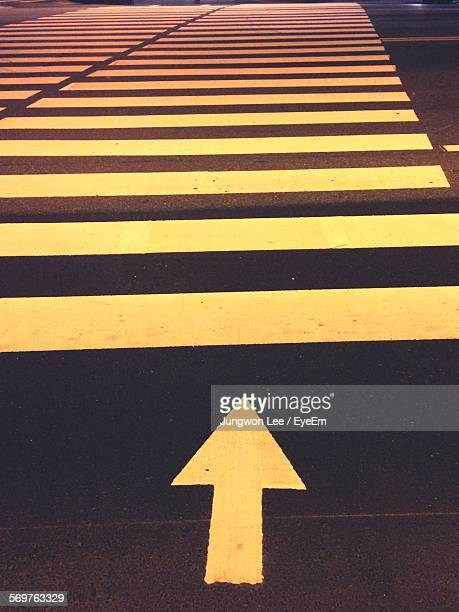 High Angle View Of Arrow Sign Leading Towards Zebra Crossing On Road At Night
