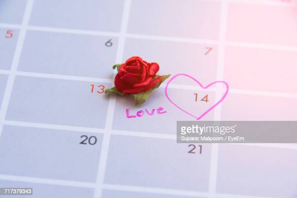 High Angle View Of Artificial Red Rose By Heart Shape And Text On Calendar