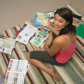 High angle view of Asian woman looking at travel brochures