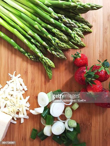 High Angle View Of Asparagus With Cheese And Strawberries On Table