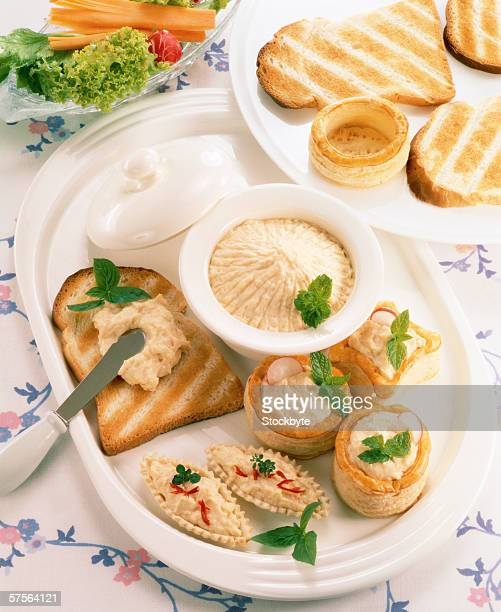 high angle view of assorted appetizers served with toast and a dip on a dining table