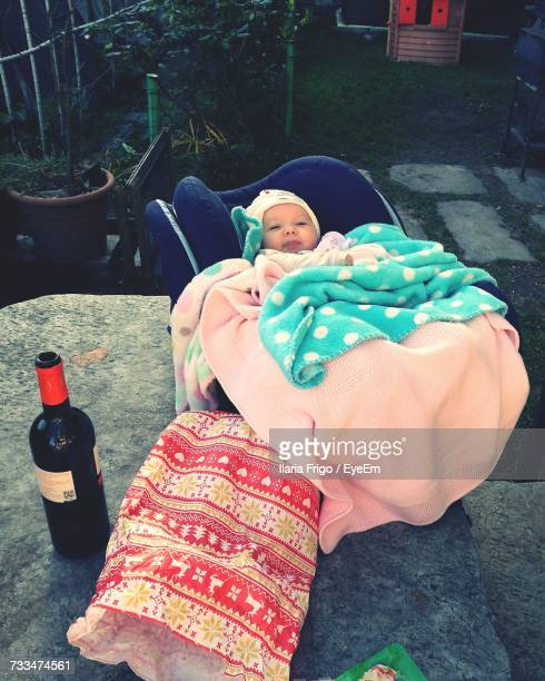 High Angle View Of Baby Lying In Stroller By Bottle