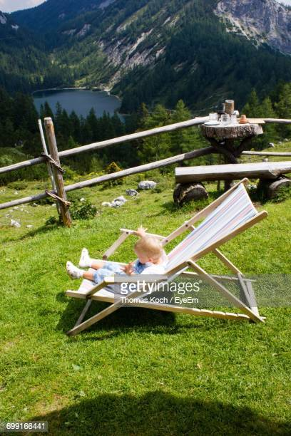 High Angle View Of Baby Relaxing On Deck Chair