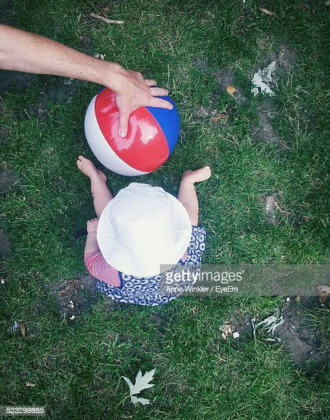 High Angle View Of Baby Sitting On Grass With Father Hand Holding Ball